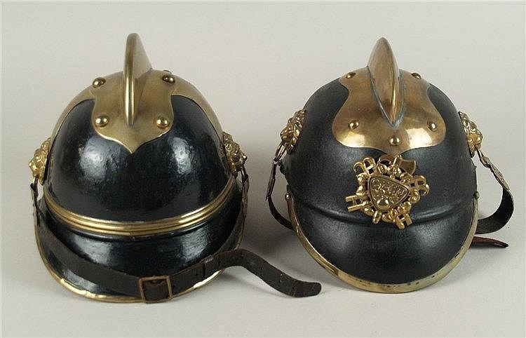 Zwei Feuerwehrhelme - Tschechien, Metallkamm, innen Lederfutter, lederner Kinnriemen mit Befestigungen in Löwenkopfform, vorne Wappen bez.''CZHJ'', H.ca.18cm, Gebrauchsspuren