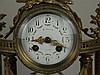 Portaluhr - portalartiger Aufbau mit vier Säulen mit Kapitellen auf segmentförmigem Sockel aus rotem weiß geädertem Marmor, dazwischen trommelförmiges Uhrwerk, Emailzifferblatt mit arabischen Ziffern, arab. Minuterie und Floraldekor, Schlag auf