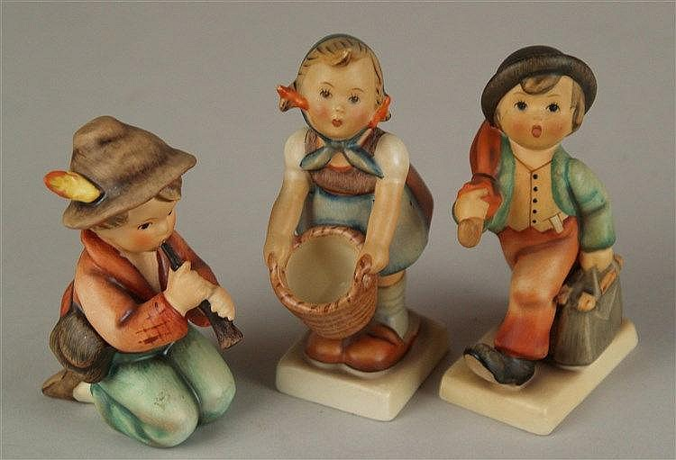 Konvolut Hummelfiguren Goebel - 3 Teile, polychrom bemalt, 1: Junge mit Regenschirm, 1970er, H.ca.10,5cm; 2:Flötenspieler, um 1980, H.ca.10cm; 3:Mädchen mit Korb, 1950er, leicht beschädigt, H.ca.12cm