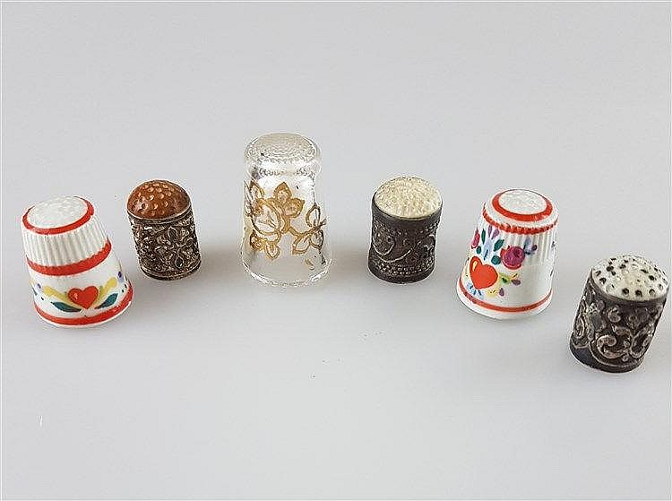 Konvolut Fingerhüte - 6 Stück,1x Glas mit Golddekor,2x Porzellan mit volkstümlichem Floralmotiv,3x kaukasisch: wohl Silber mit Reliefmuster und Bein-bzw. Hornkappe,H.ca.2-3cm