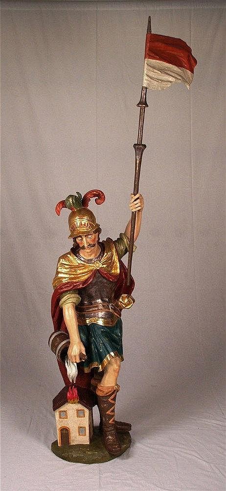 Holzfigur ''Hl.Florian'' - Hl.Florian bei der Feuerbekämpfung, stehende Figur mit Fahne, Lindenholz, farbig gefasst,tlw. vergoldet, H.ca.130cm, mit Fahne ca.210cm, auf gerundetem Sockel,an der Haustür signiert u. 1984 datiert