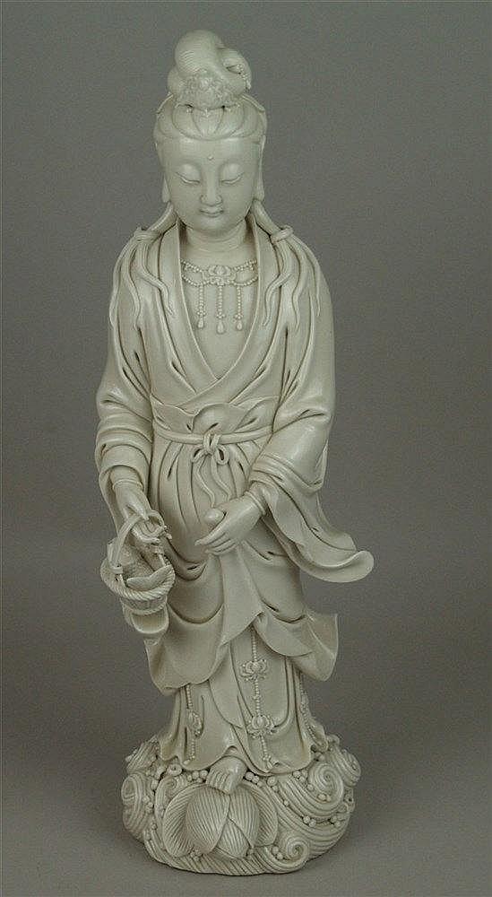 Figur der Guanyin mit Fischkorb - Blanc-de-Chine, Dehua-Porzellan, China 20.Jh.,feine Weißporzellanplastik,Darstellung der Göttin der Barmherzigkeit auf einem mit Perlen und Lotosknospe bestücktem Wellensockel stehend,die Haare aufgesteckt und mit