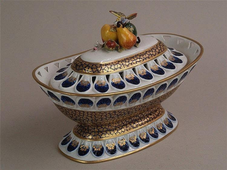 Deckelschale - Sèvres, Modell et decoration exclusive a la Main, reicher Goldornamentdekor auf Kobaltblau, durchbrochener Goldrand, Deckel mit figürlichem Knauf, ein Blatt beschädigt, H.ca.22cm