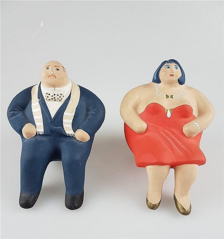 Keramikfiguren - Korpulente Dame & Herr sitzend, polychrom bemalt, Nase bei der männlichen Figur leicht bestoßen, an der Seite undeutlich sign. u. dat. ''86'' u. ''87'', H.ca.14cm
