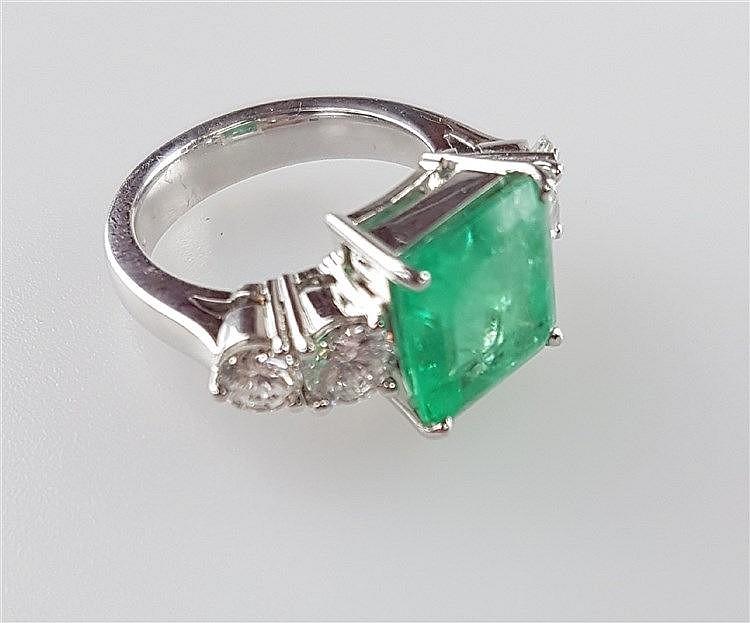 Smaragdring - massive Weißgold-Ringschiene gestempelt 750, Gewicht ca.8,6g, Ringkopf besetzt mit zentralem quadratischem Smaragd im Smaragdschliff(Steinmaß ca.10x10mm),flankiert von je zwei Diamanten im Brillantschliff zus.ca.0,9ct.( 2x ca.0.20/2x