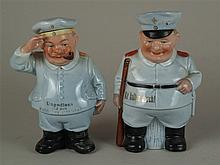 Zwei Figuren-/Scherzflaschen - Flaschen in Form zweier Wachmänner (?) in Uniform gestaltet,Mützen jeweils an Korkstopfen ausgeführt,farbig staffiert,mit Sinnsprüchen in Goldbuchstaben,H.ca.16,5/17,5cm