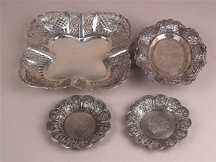 4 Schalen - versilbert/Silber, 2x rund D.ca.11cm, 1x oval L.ca.16cm, auf 3 Standfüßchen, H.ca.4cm,Relief- und Gravurdekor mit volkstümlichen Szenen, 1x vierpassig ca.20x20cm,durchbrochen gearbeiteter Rand mit Floralzier