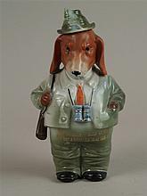Figurenflasche - Flasche in Form eines aufrecht stehenden Hundes in voller Förstermontur mit Gewehr gestaltet,Hut an Korkstopfen ausgeführt,Unterglasurbemalung,mit Sinnspruch in Goldbuchstaben,H.ca.22cm