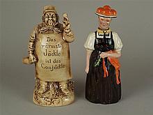 Zwei Figurenflaschen - Flaschen in Form eines Schwarzwaldmädels sowie eines Kellermeisters,Kopf mit Hut an Korkstopfen ausgeführt,1 Stopfen fehlt,farbig bzw.monochrom staffiert,H.ca.24 cm