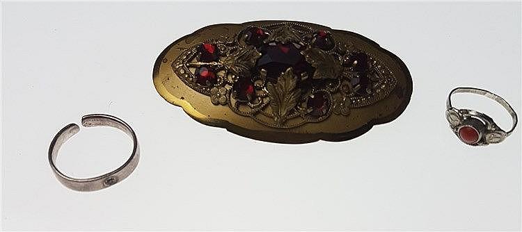 Konvolut - 3-tlg: 1 Metallbrosche mit Jugendstil-Ornamentik und roten Glassteinen,L.ca.55mm/ 2 Kinderringe, Silber, einmal Korallenbesatz, D.ca.13/15mm, Gebrauchs- u. Altersspuren
