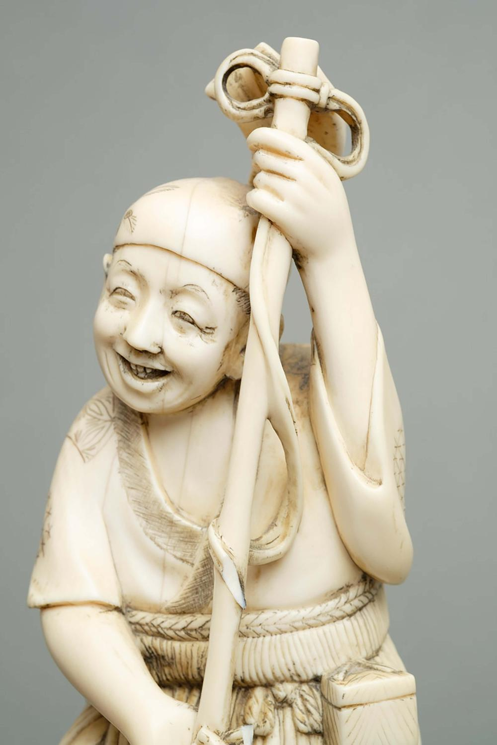 Ivory okimono of a fisherman spearing fish with a trident on a wooden stand
