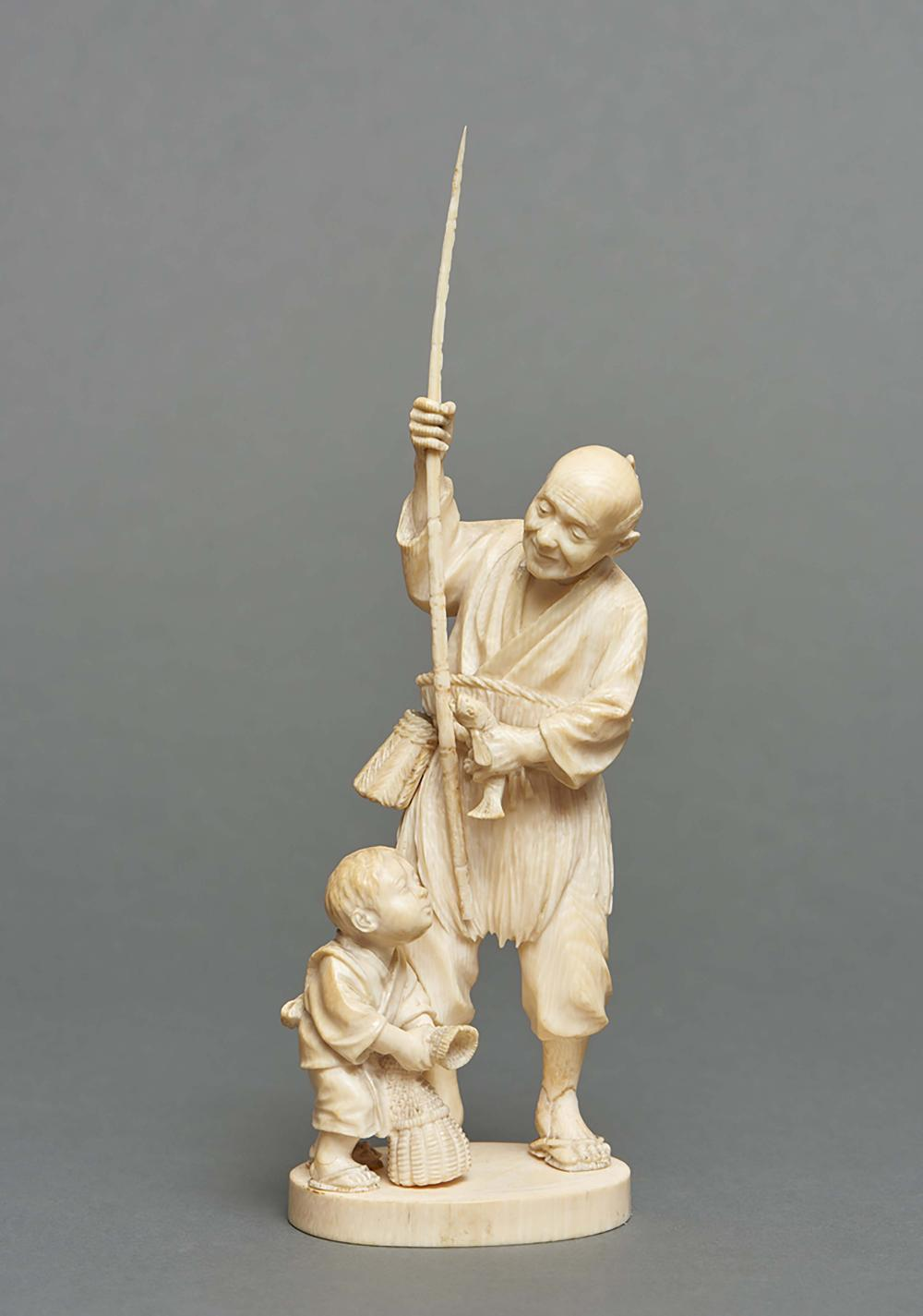 Ivory okimono of a fisherman holding a rod and a fish in his hands with his