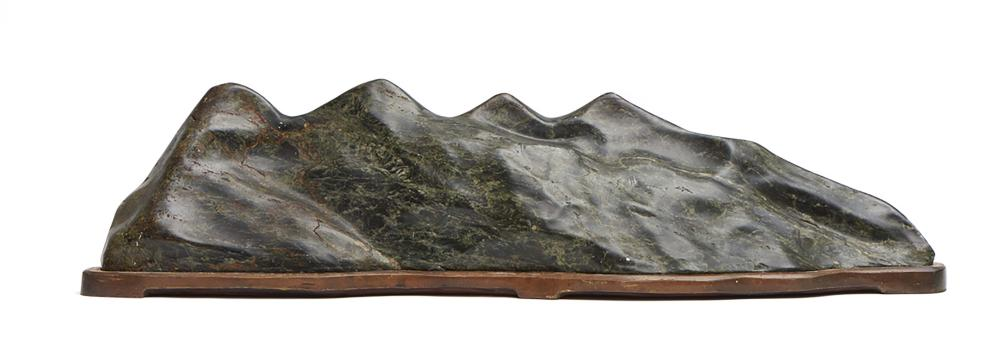 Polished black suiseki-stone with some dark brown and dark green on a woode