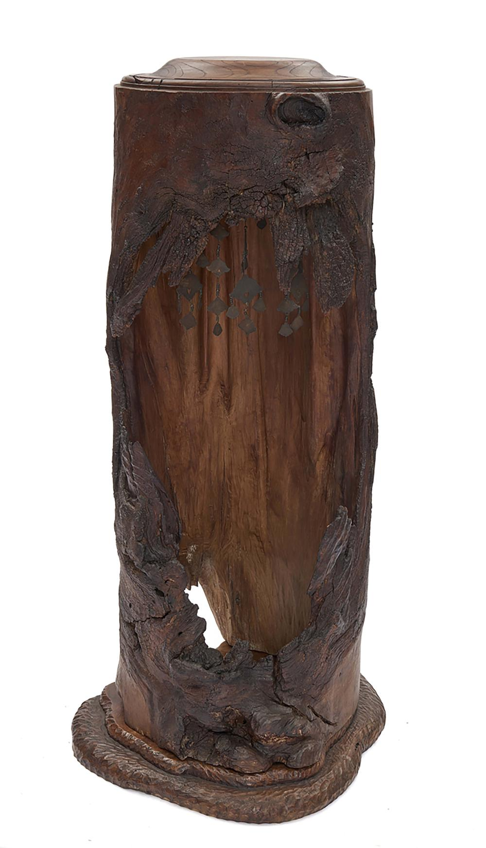Hollowed out wooden trunk on a plinth used as a kind of shrine in which a s