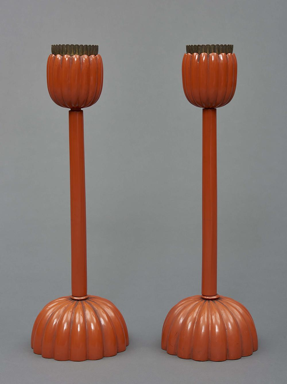 A pair of orange-red lacquered candlesticks with a chrysanthemum foot, used