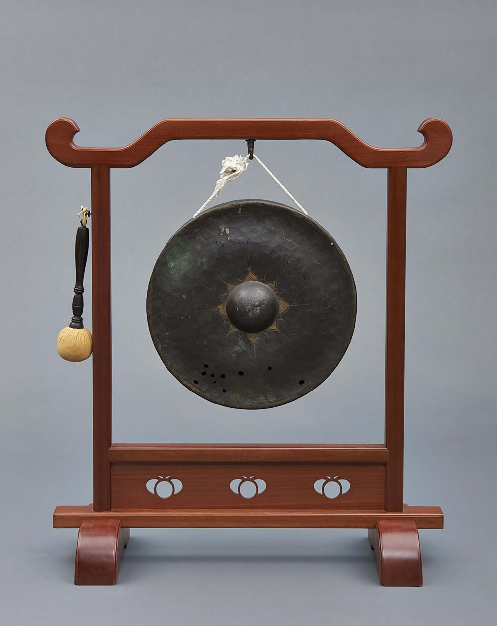 A suspended gong hanging in a hardwood lacquered frame together with a mall