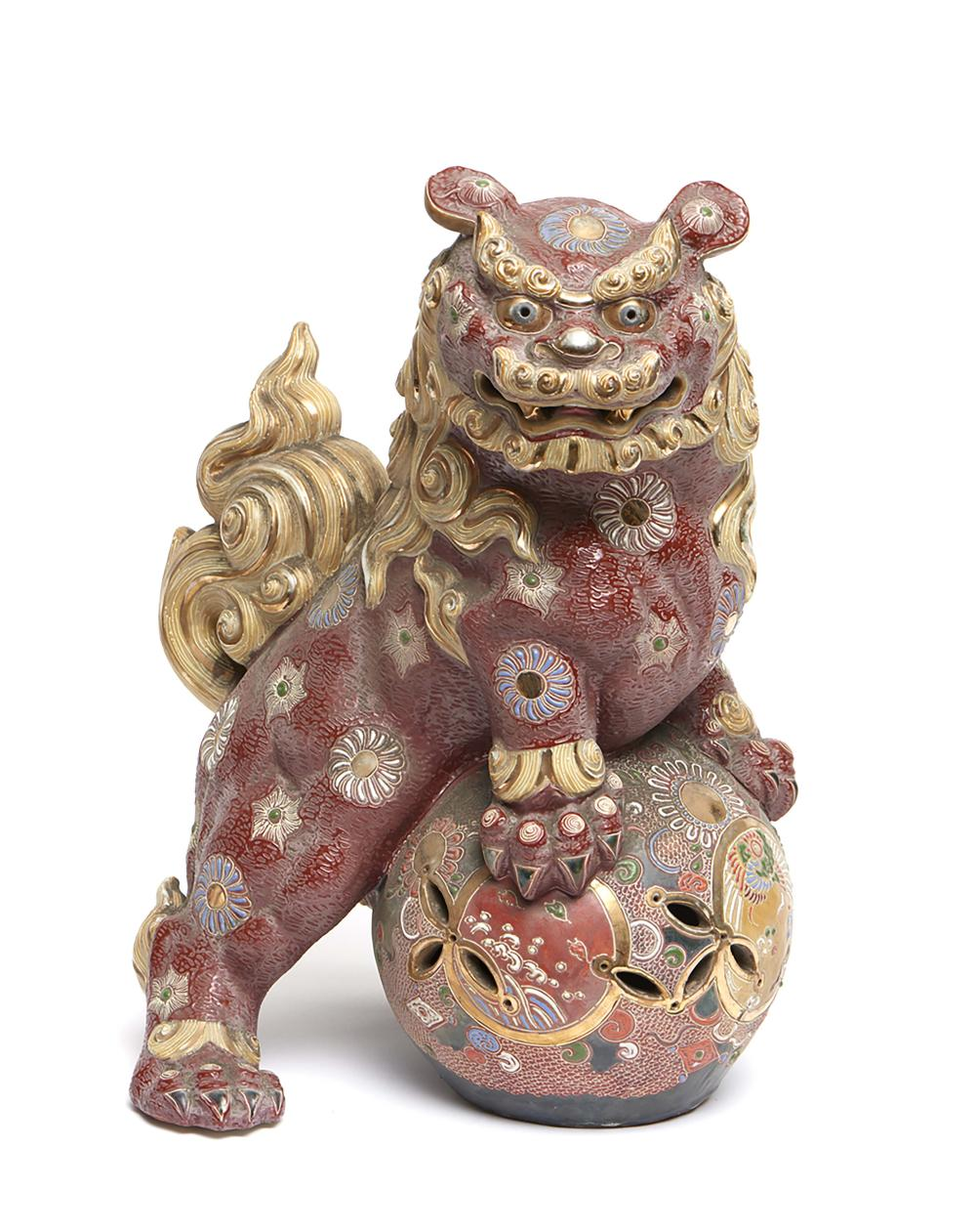 Satsuma-ware figure of a red glazed shishi-lion standing on an open-work ba