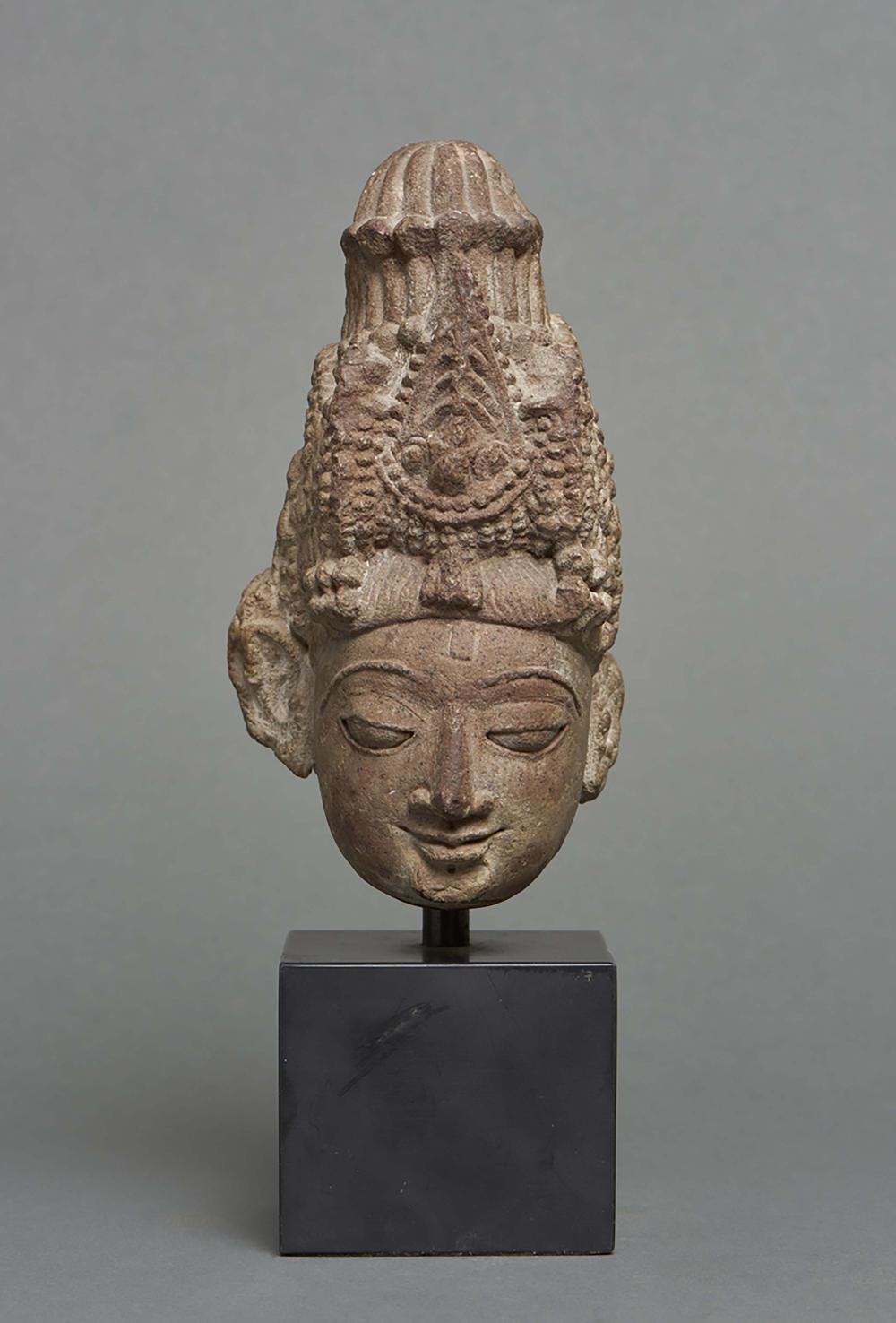 Stone head on a stand depicting the Indian god Shiva. On a plinth. India, 1