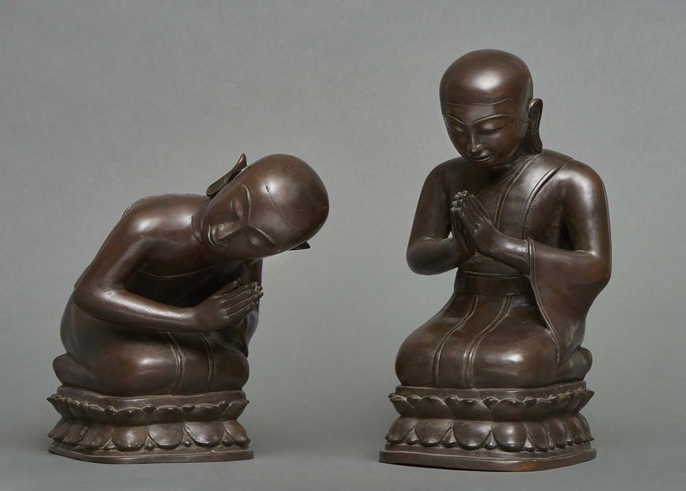 Two heavy dark bronze figures of young buddhist monks bowing in prayer. Tha