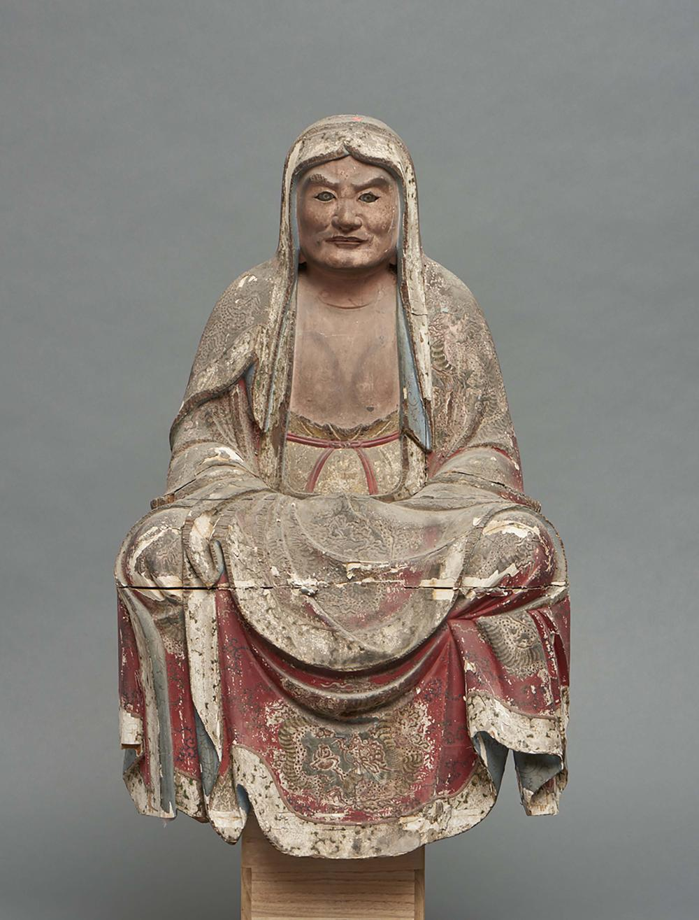 Wooden figure of the Zen patriarch Daruma with traces of polychromy sitting
