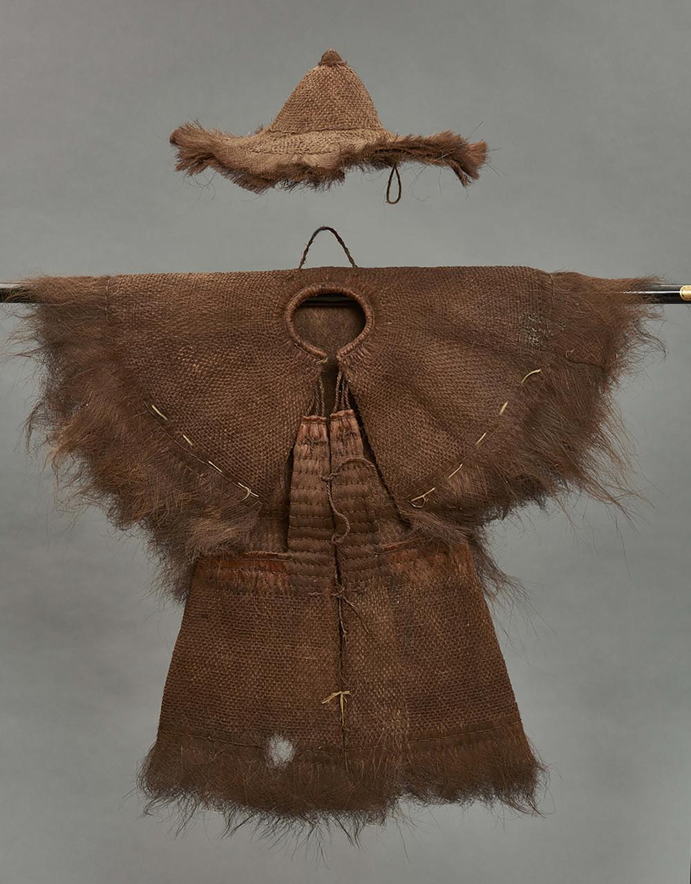 Straw raincoat (mino) used by fishermen and farmers together with a matchin