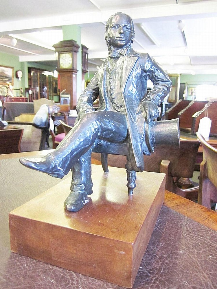 John Doubleday (British, born 1947) A commemorative bronze maquette of Isambard Kingdom Brunel Modelled in seated pose with head turned to sinister, holding his top hat in his left hand, his legs crossed, signed and dated 1983 to the seat rail, 24cm,