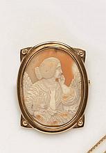 Broche  en or jaune retenant un camée coquille représentant une scène quotidienne de mère et fille de profil.  Monture vers 1910.  Poids Brut : 24,38 g.