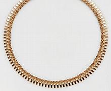 Collier articulé  en or jaune orné de barrettes ciselées d'un motif floral.  Long. 45 cm Poids. 44 g