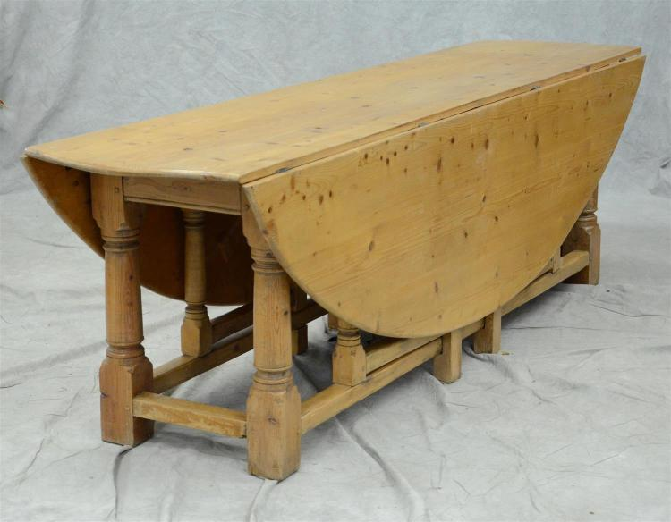 Scrubbed pine stretcher base harvest table, rounded leaves, base with turned legs and outside stretchers, the leaves supported by do...