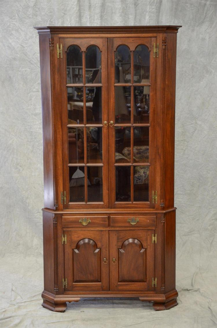 Walnut 2 pc corner cupboard by Pender-Butler, c 1970''s, top section with 2 glazed doors with arched top panes, base with 2 drawers o..