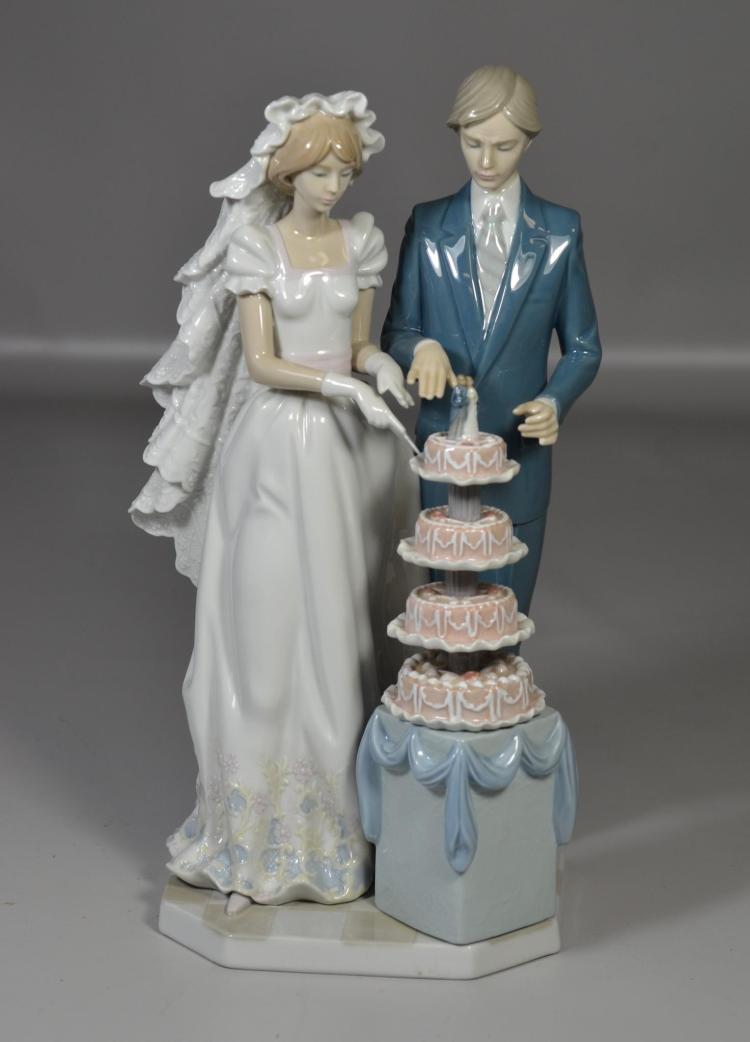 Lladro figurine of a bride and groom cutting a tiered wedding cake, Lladro mark on base No. 5587, 12 1/2