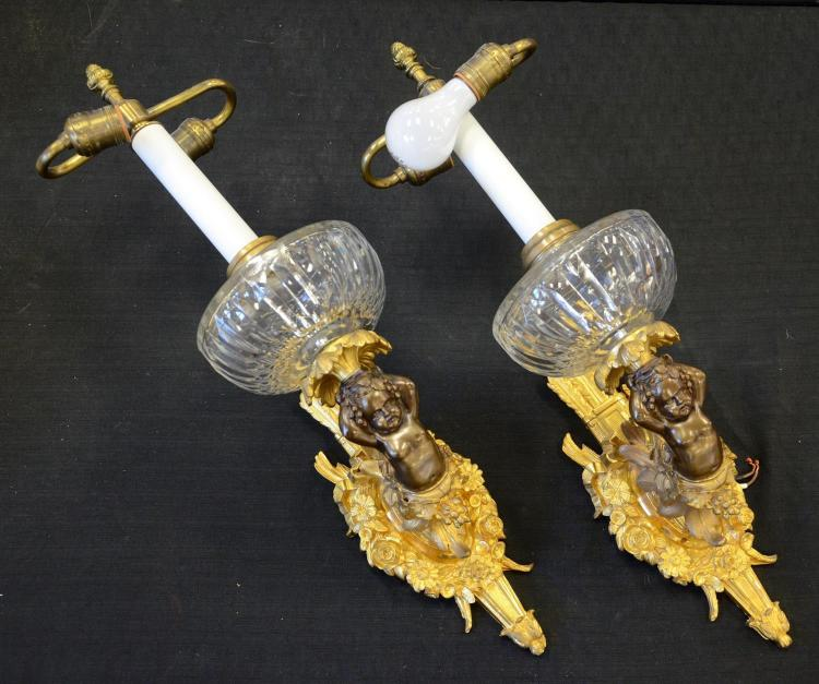 Fine pair of French ormolu sconces with fire gilt bronze backs with feathers, flowers, etc, and patinated half cherubs holding aloft...