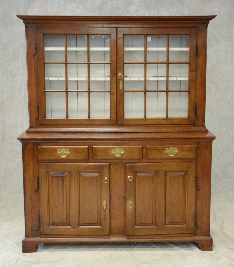 Walnut 2 pc stepback Dutch cupboard, top section with 2 glazed 9 pane doors, flanked by smooth inset quarter columns, bottom with 3...