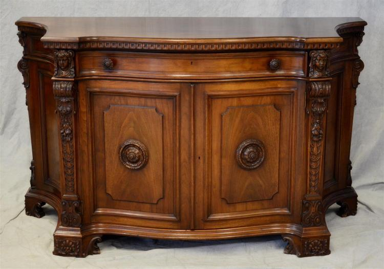 Figural carved server, walnut frame with carved figures on post, floral and plume decoration, one drawer over 2 doors with fitted in...