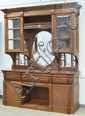 Monumental Carved Mahogany Eastlake  Victorian Sideboard, the top section with display cabinets with beveled glass panels flanking a...