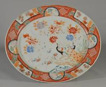 Kutani oval platter, Meiji Period (1868-1912), the interior decorated with two ho-o birds in foliage surrounded by an iron-red and p...