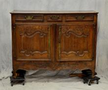 French Provincial carved oak buffet, 18th C, floral carved decoration on doors and skirt, three drawers over two doors, some losses...