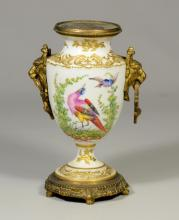 Sevres-style gilt bronze-mounted porcelain urn, lions head handles with ring pulls, handpainted wild birds, gold anchor maker's mark..