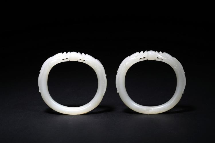 A PAIR OF WHITE JADE DRAGON BRACELETS