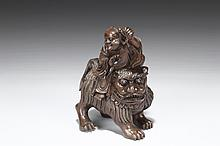A CARVED BAMBOO FIGURE OF IMMORTAL ON A LION