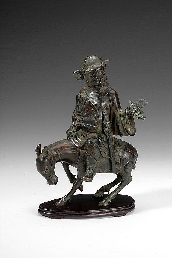 A CHINESE CARVED BRONZE FIGURE OF A MAN RIDING A DONKEY