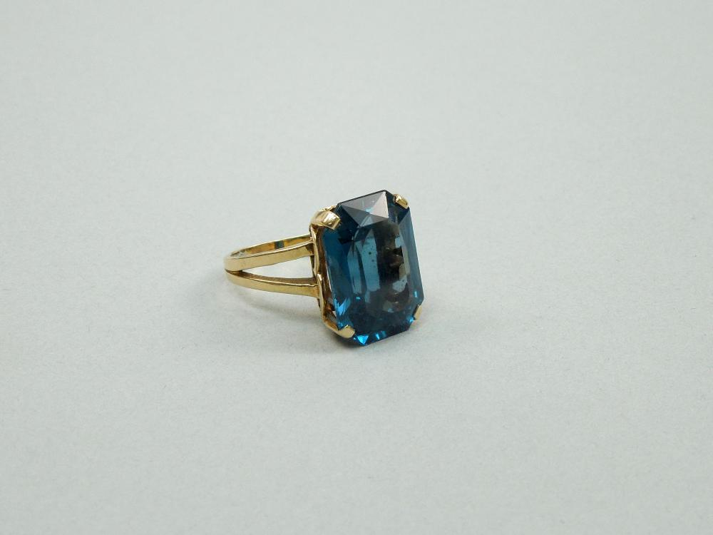 14K YELLOW GOLD RING WITH FACETED BLUE STONE.