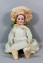 A Schoenau and Hoffmeister No. 914 12 1/2, bisque headed doll with blue closing eyes and open mouth showing two teeth and with jointed composition body, 27ins high, dressed in white lawn full length dress <br>Provenance: Bonham's Auction - 10th August 1997 - Lot 1013