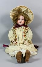 An Armand Marseille No. 390-15 bisque headed doll with brown closing eyes and open mouth showing five teeth, and with jointed composition body, 31ins high, wearing cream wool coat with red floral embroidery <br>Provenance: Bonham's Auction - 10th August 1997 - Lot 1017