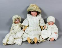 A late 19th Century Armand Marseille No.390A8M bisque headed doll with opening blue eyes, open mouth, showing four teeth and with jointed composition body, 24ins high, together with two others, various