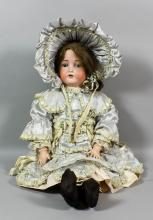An early 20th Century Bruno Schmidt bisque headed character doll (BSW), with opening blue eyes, open mouth showing four teeth and composition body, 25.5ins high