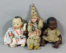 A late 19th Century bisque headed pierrot boy doll, No. 70.205, with open blue eyes, open mouth showing two teeth and wood wire jointed body, 14.5ins high, together with a bisque headed African baby doll and bisque headed Chinese baby doll