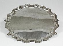 A George V silver circular salver with shaped and