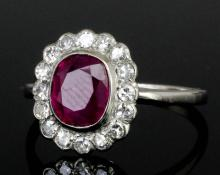 A modern silvery coloured metal mounted ruby and diamond ring, the central cushion cut ruby approximately 1.90ct, contained within a border of sixteen small brilliant cut diamonds (gross weight 2 grammes - ring size N 1/2) <br>Note : With Gemmological Certification Services Report No. 5775-2674 dated 28th July 2015, confirming the stone to be a natural ruby of Burma origin with no indication of heat treatment