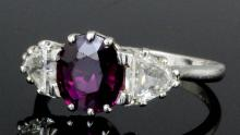 A modern platinum mounted ruby and diamond three stone ring, the central circular cut ruby approximately 1.70ct,  shouldered by two tear cut diamonds, each approximately .50ct, (gross weight 5.1 grammes - ring size Q 1/2)